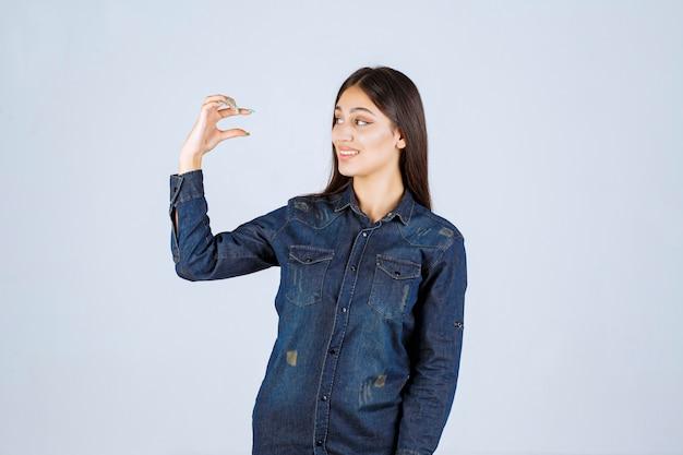 개체의 측정 값을 보여주는 데님 셔츠에 젊은 여자