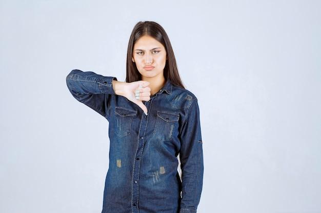 Молодая женщина в джинсовой рубашке показывает палец вниз
