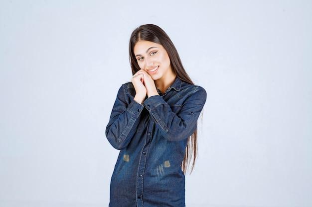 笑顔とかわいい顔を作るデニムシャツの若い女性