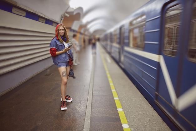 데님 반바지를 입은 젊은 여성이 지하철 기차 옆에 서 있습니다.