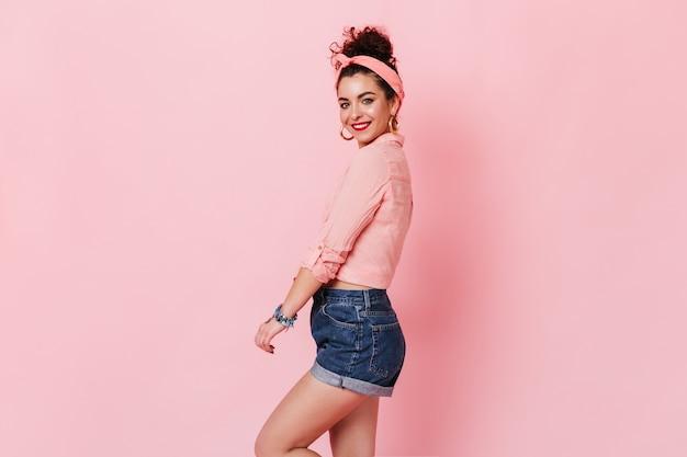 데님 반바지, 핑크 블라우스와 머리띠 귀여운 고립 된 공간에 웃 고있는 젊은 여자.