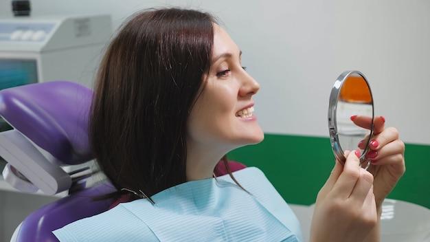 歯科用椅子の若い女性は、治療後、鏡で自分の歯を調べます。側面図。歯のケアのコンセプト。