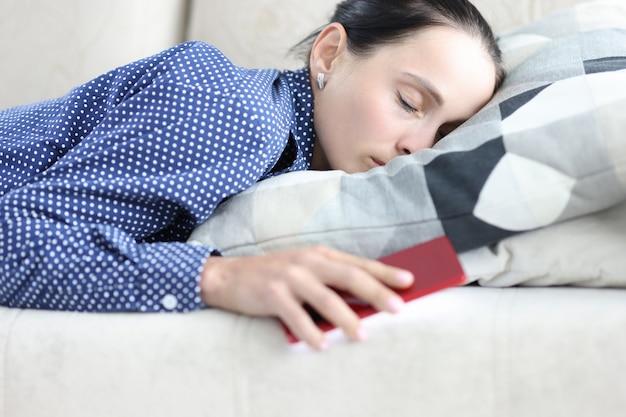 우울증에 걸린 젊은 여성은 남자의 전화나 sms를 기다리는 휴대전화를 들고 소파에 누워 있다