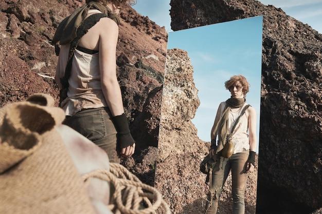 鏡の前に立って屋外で自分を見ている汚れた服を着た若い女性