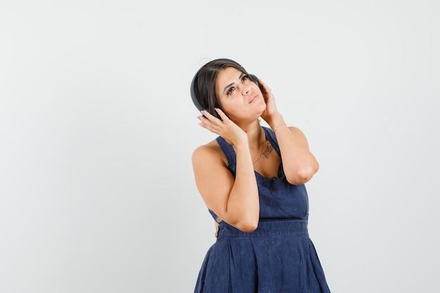 ヘッドフォンで音楽を楽しんで、夢のように見えるドレスを着た若い女性