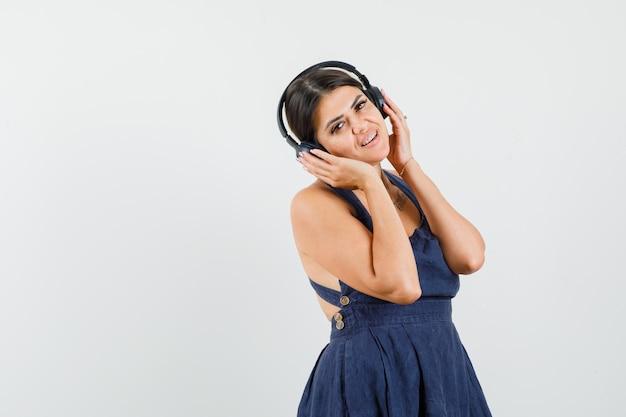 ヘッドフォンで音楽を楽しむドレスを着た若い女性
