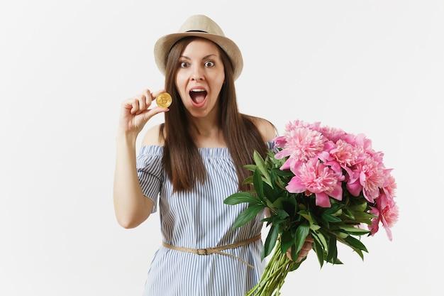 ドレスを着た若い女性、ビットコインを保持している帽子、黄金色のコイン、白い背景で隔離の美しいピンクの牡丹の花の花束。ビジネス、配達、オンラインショッピング、仮想通貨の概念。