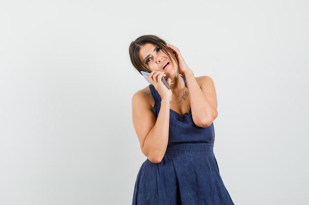 Молодая женщина в платье разговаривает по мобильному телефону и выглядит задумчивой