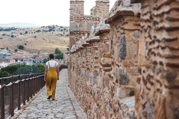 바지를 입은 젊은 여성이 스페인 아빌라의 중세 도시 성벽을 따라 걷고 있습니다.