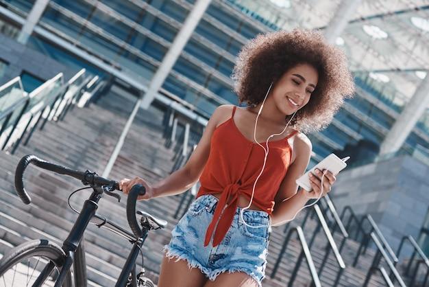 Sの近くを歩いている通りでイヤホンフリースタイルの若い女性