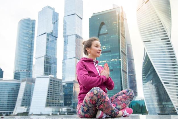 Молодая женщина в easy seat позирует против небоскреба