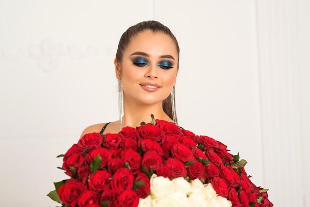 Молодая женщина в элегантном платье держит букет из ста красных роз
