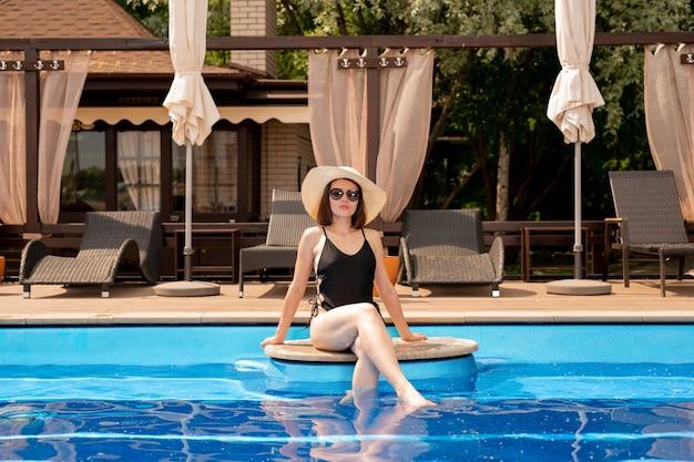 Молодая женщина в элегантной шляпе и купальниках сидит у бассейна, опустив ноги в воду