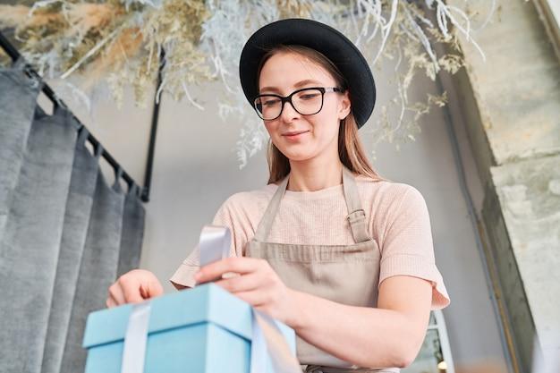 眼鏡と帽子の結び目を結ぶとリボンをリボンにバインドしながらpofギフトボックスに弓を作る若い女性