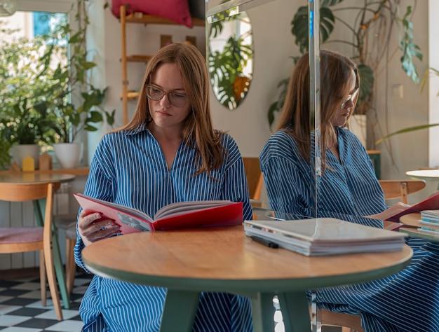 Молодая женщина в очках читает книгу в современном кафе с растениями и читателем дневного света в кофейне