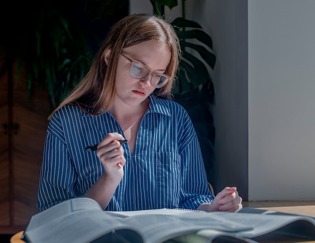 안경을 쓴 젊은 여성이 나무 책상에서 공책을 들고 시험 준비를 하며 독서를 생각하고 있습니다.