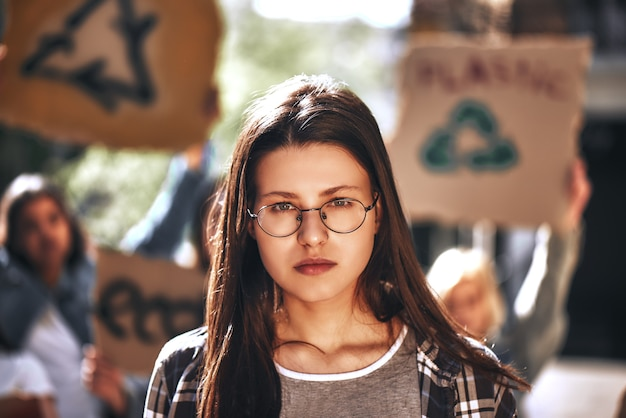 간판을 들고 여성 시위대의 그룹과 안경에 젊은 여자