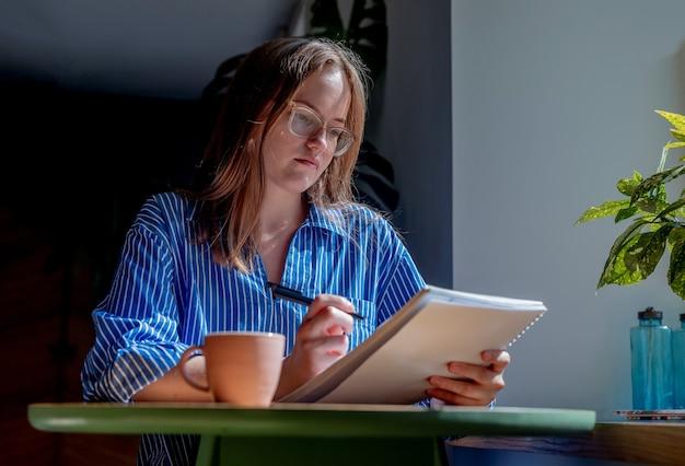 Молодая женщина в очках писать ручкой в блокноте, делая заметки в кафе с чашкой кофе на столе