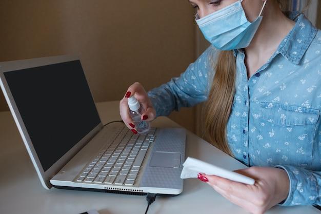 彼女の職場のガジェットの表面を消毒するフェイスマスクの若い女性