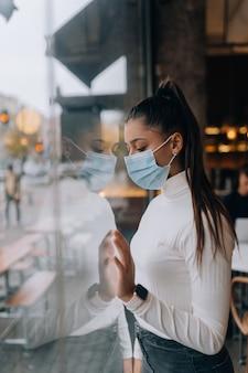 カフェの窓の前に立っているフェイスマスクの若い女性