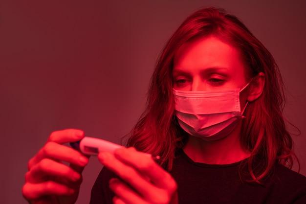 赤い光の中で立って、デジタル温度計で温度をチェックするフェイスマスクの若い女性
