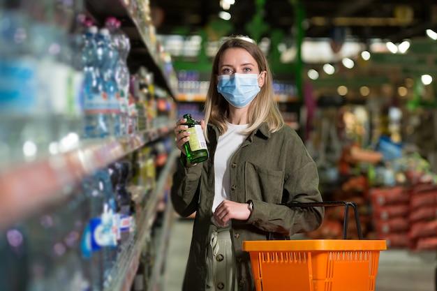 Молодая женщина в маске ходит между супермаркетом рядов с корзиной в руках. женский шоппинг через раздел товаров, просмотр. большой магазин с множеством проходов. в продуктовом магазине выбирает товар осматривая
