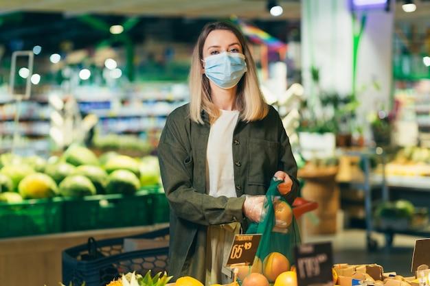 Молодая женщина в медицинской защитной маске на лице выбирает и собирает в эко-сумке овощи или фрукты в супермаркете женщина, стоящая на рынке продуктового магазина возле прилавка, покупает в многоразовой упаковке