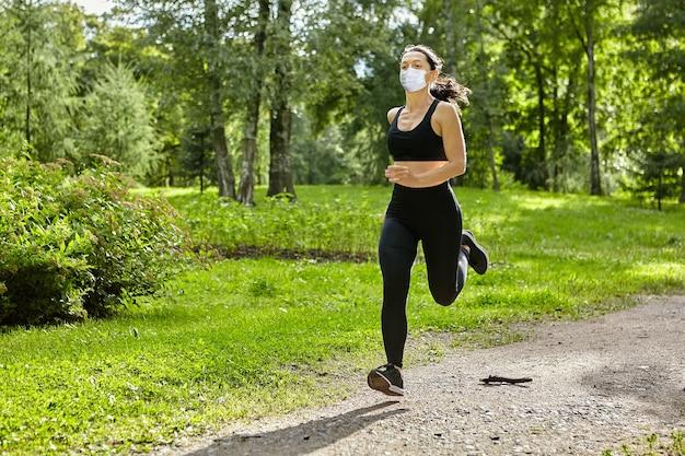 코로나 바이러스 코로나 19 전염병 중 보호로 얼굴 마스크를 쓴 젊은 여성이 실행 중입니다.
