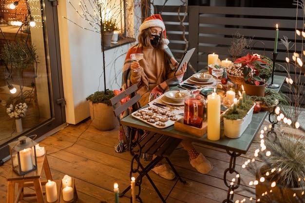 Молодая женщина в лицевой маске празднует одни новогодние праздники дома. концепция карантина и самоизоляции во время эпидемии в праздничные дни