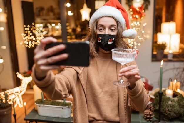 Молодая женщина в лицевой маске празднует в одиночестве новогодние праздники дома, имея видеозвонок по телефону с друзьями. концепция карантина и самоизоляции во время эпидемии в праздничные дни