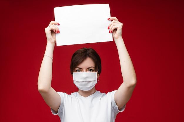 빈 종이 들고 바이러스 전염병으로부터 보호하기 위해 얼굴 마스크에 젊은 여자