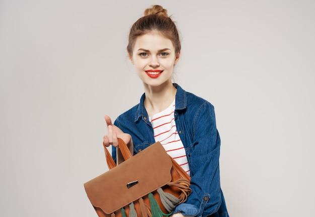 ファッショナブルな服を着た若い女性楽しいバックパック学校