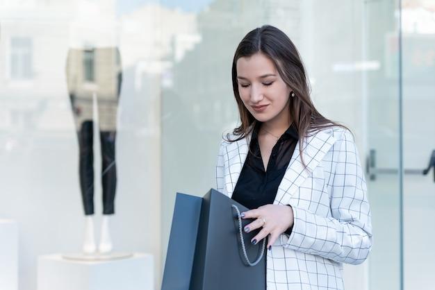 Молодая женщина в модной одежде держит черный пакет для покупок на фоне витрины.