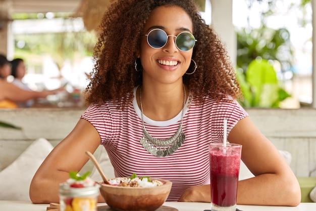 ファッショナブルな丸い色合いの若い女性は、新鮮な飲み物を飲み、おいしいエキゾチックな料理を食べます