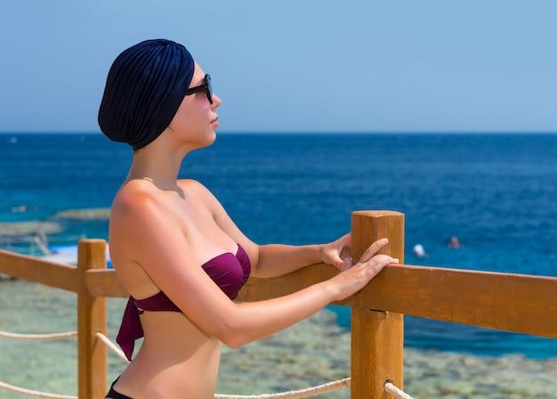 Молодая женщина в женском тюрбане и солнечных очках стоит перед деревянным забором с веревочными вставками на пляже и смотрит на красивое море