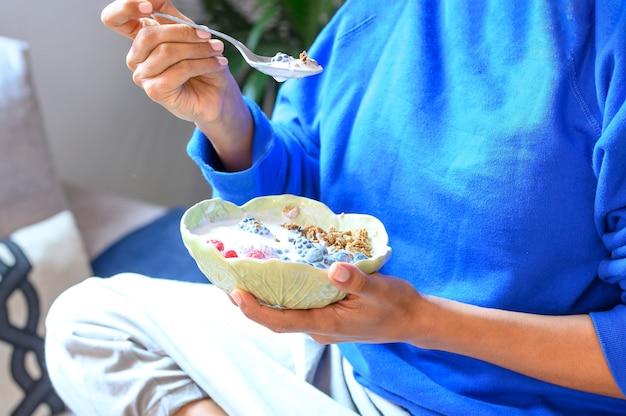 自宅で健康的な朝食をとっているフィットネス服の若い女性、クローズアップ