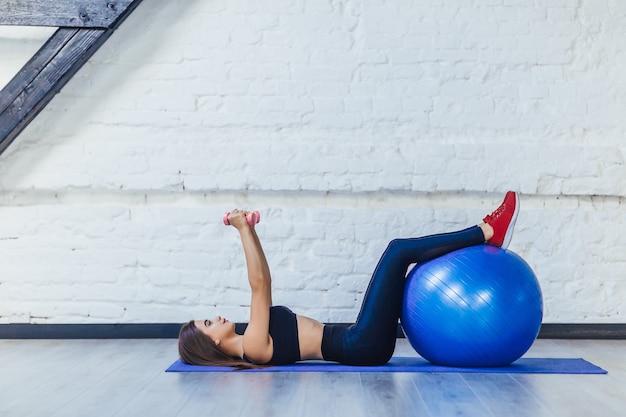Молодая женщина в фитнес-одежде, тренирующейся с фитнес-мячом и гантелями, изолированными на белой комнате.