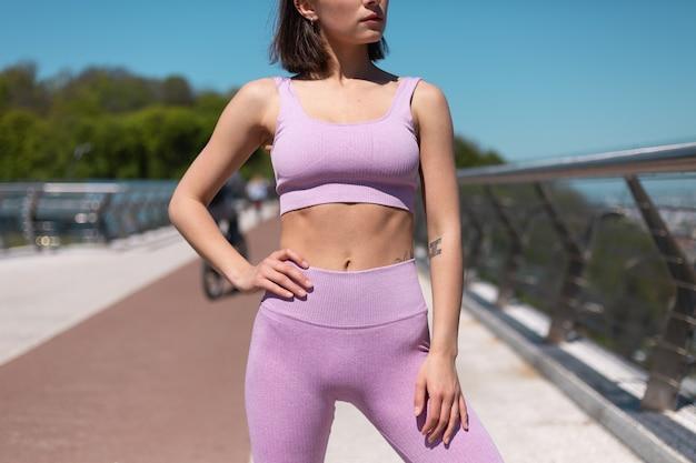Молодая женщина в спортивной одежде на мосту в жаркое солнечное утро подходит, показывая свой пресс и фигуру, спортивную мотивацию