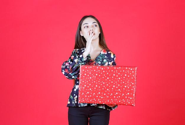 その上に白い点が付いている赤いギフトボックスを保持し、口に手を入れて誰かを呼び出す花柄のシャツの若い女性