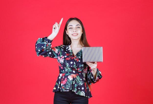 銀のギフトボックスを保持し、良いアイデアを持っている花柄のシャツの若い女性