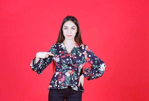 붉은 벽에 서서 자신을 소개하는 꽃무늬 셔츠를 입은 젊은 여성