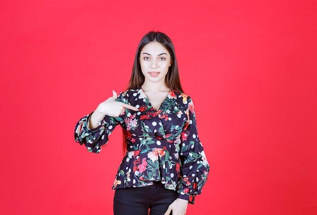 赤い壁に立って、自分自身を提示する花柄のシャツを着た若い女性