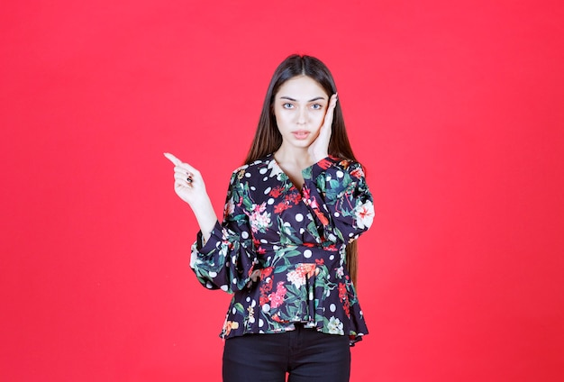 赤い壁に立って左側を示す花柄のシャツを着た若い女性