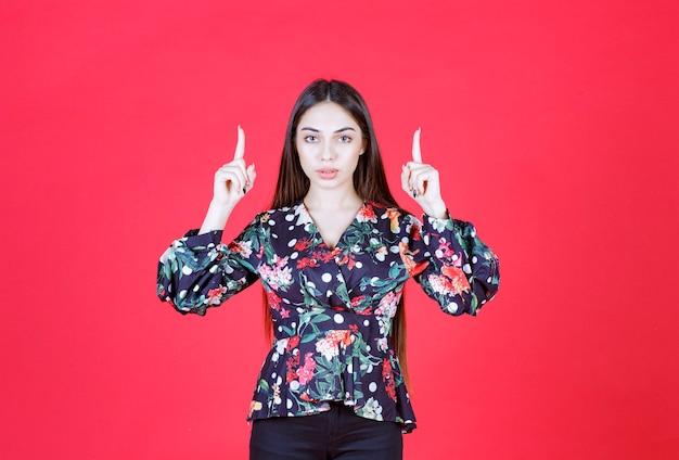 赤い壁に立って逆さまに見える花柄のシャツを着た若い女性