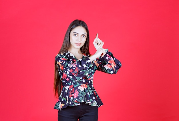 빨간 벽에 서서 거꾸로 보여주는 꽃무늬 셔츠를 입은 젊은 여자