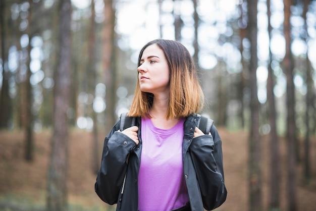 Молодая женщина в лесу, глядя в сторону