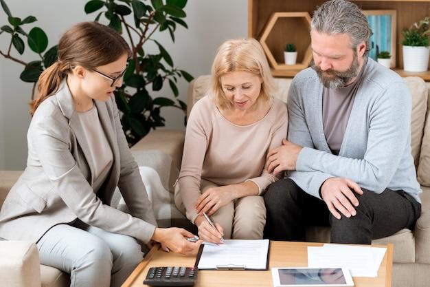 Молодая женщина в формальной одежде, указывая на место для подписи, пока зрелый клиент подписывает документ после переговоров