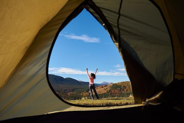 Молодая женщина перед туристической палаткой, вид изнутри, на фоне древесных холмов и голубого неба.