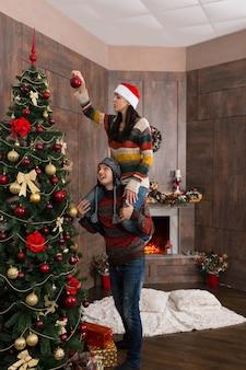 彼女のボーイフレンドの首に座って、装飾された暖炉のあるリビングルームの大きなクリスマスツリーに装飾を掛ける面白い帽子をかぶった若い女性