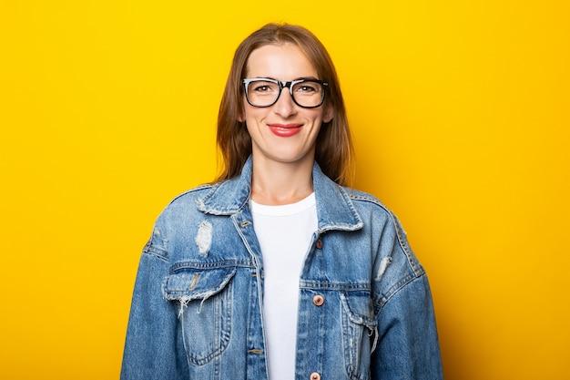 黄色の壁にメガネとデニムジャケットの若い女性。